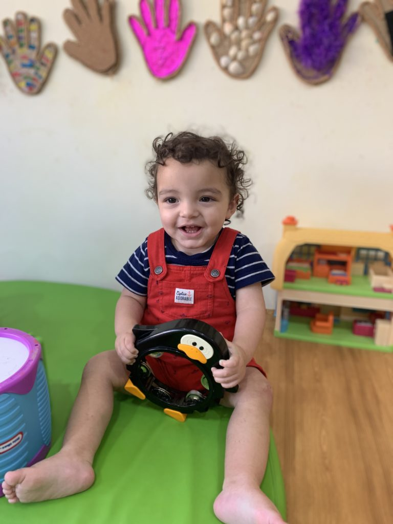 Toddler playing with musical instrument during nursery class