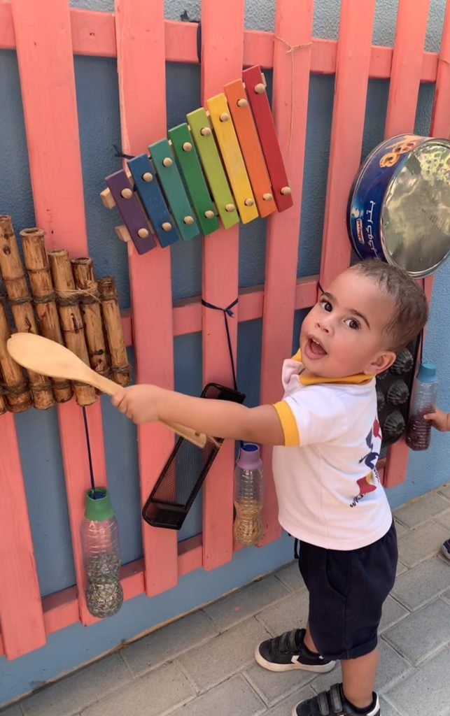 Toddler boy playing with different kinds of xylophones