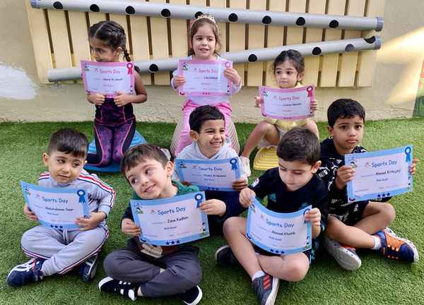 Nursery school students showing off their Sports Day certificates