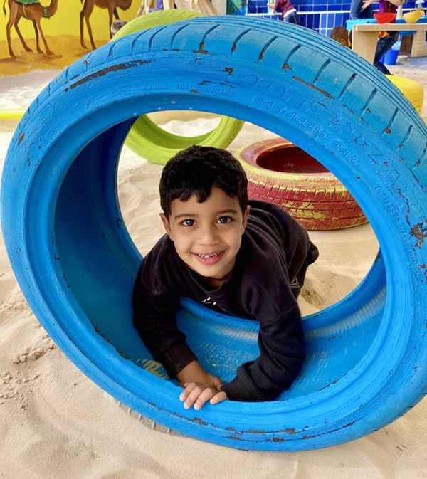 Happy kid playing with blue wheel in sandbox outdoor play area