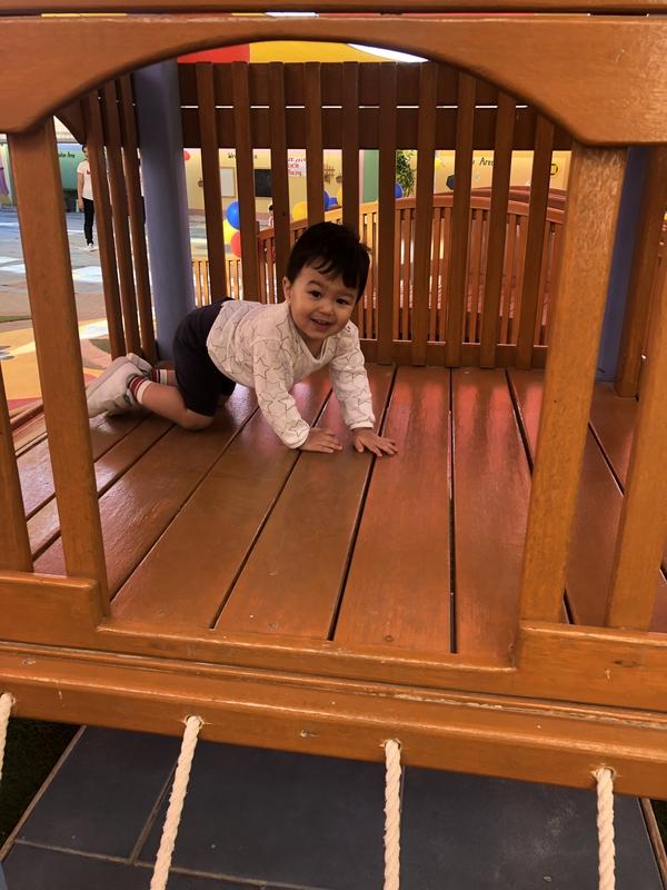 Toddler crawling inside climbing playground set